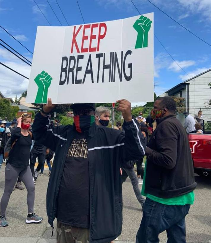 "Anthony Austin holds ""Keep Breathing"" sign during anti-racism protest, June 7, 2020"