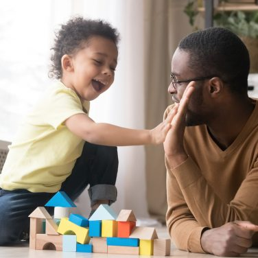 African American father in glasses with toddler son playing with colorful wooden constructor, giving five, adorable little child and black dad or babysitter having fun on warm floor at home